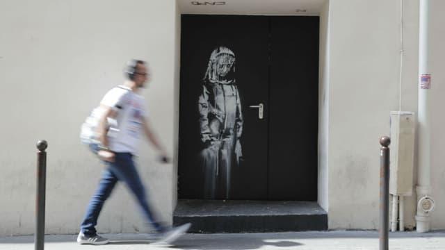 Peinture au pochoir réalisée par Banksy sur une porte du Bataclan en juin 2018