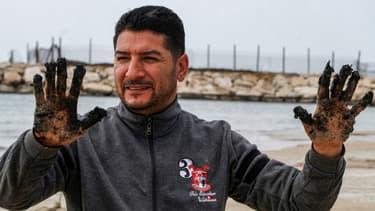 Hussein Hamza, un activiste environnemental libanais, montre ses mains couvertes de sable imbibé de goudron dans la réserve naturelle de Tyr, au sud du Liban, le 22 février 2021.