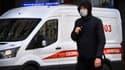 Un homme portant un masque à côté d'une ambulance à Moscou, en Russie, le 23 mars 2020