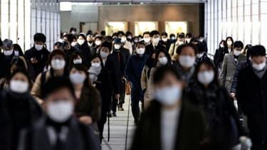 Des Japonais à la gare de Shinjuku, le matin, à l'heure de pointe, le 4 janvier 2021 à Tokyo