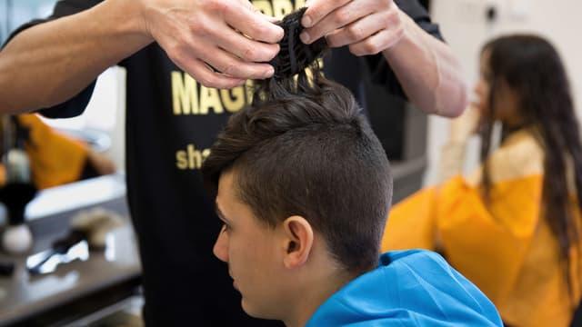 """Shalom Koresh accroche une """"kippa magique"""" sur un client de son salon de coiffure de Rehovo, en Israël."""