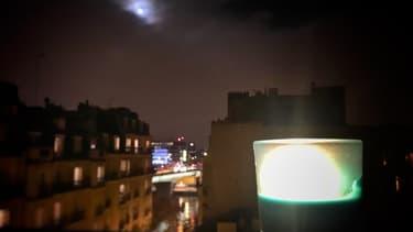 Les citoyens rendent hommage aux victimes des attentats en allumant une bougie sur leur fenêtre