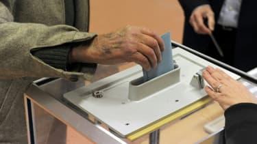 Un électeur met son bulletin dans l'urne dans un bureau de vote.