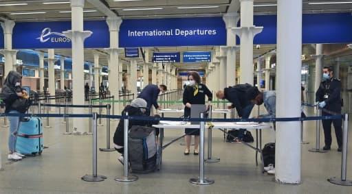 Des voyageurs équipés de masques de protection remplissent un formulaire au terminal de l'Eurostar de St Pancras, le 8 juin 2020 à Londres