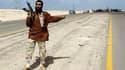 Rebelle libyen sur la route entre Benghazi et Ajdabiah. La coalition internationale a bombardé dans la nuit de dimanche à lundi les forces de Mouammar Kadhafi près d'Ajdabiah, dans l'est de la Libye, et les insurgés font route vers cette ville stratégique