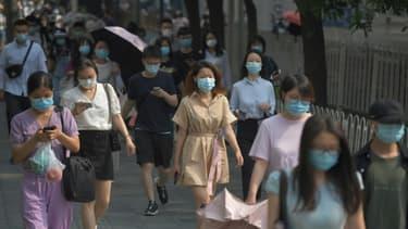 Des Chinois portent des masques de protection contre le coronavirus dans une rue de Pékin, le 28 juin 2020