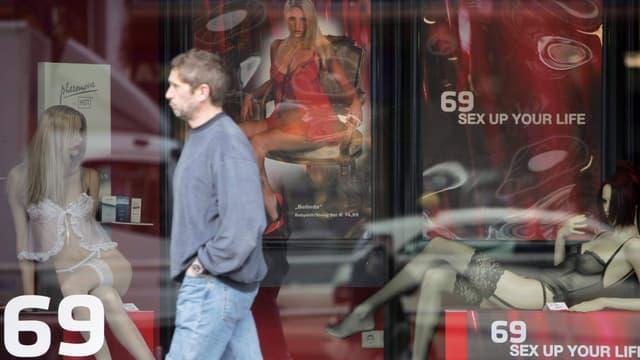 Un passant devant la vitrine d'un sex shop
