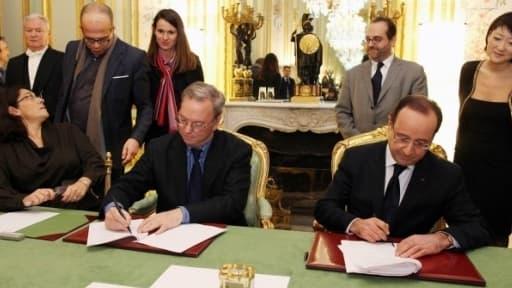 Nathalie Collin (Le Nouvel Obs), David Kessler, Aurélie Filippetti, Eric Schmidt (Google), Marc Schwartz (Mazars), François Hollande et Fleur Pellerin signant l'accord avec la presse française le 1er février