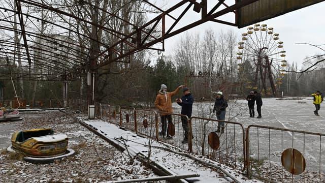 Des visiteurs marchent dans un parc d'attractions abandonné dans la ville fantôme de Pripyat, non loin de la centrale nucléaire de Tchernobyl, le 8 décembre 2020.