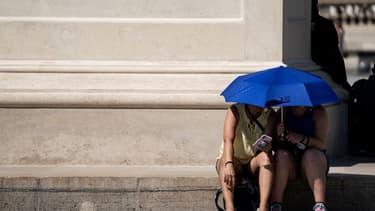 Des touristes s'abritant près de la pyramide du Louvre, pour échapper à la chaleur de ce mois de juin 2019.