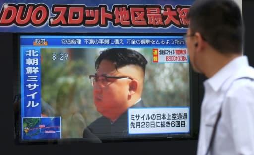 Un piéton regarde une image du leader nord-coréen Kim Jong-Un, à Tokyo le 15 septembre 2017