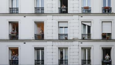 Des personnes à la fenêtre de leurs appartements applaudissent les personnels soignants, le 30 mars 2020 à Paris pendant confinement instauré en France