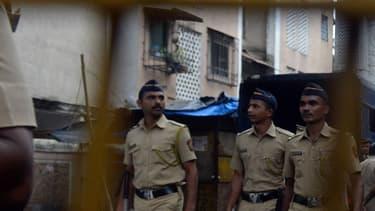 Des policiers indiens patrouillent le long d'une rue.