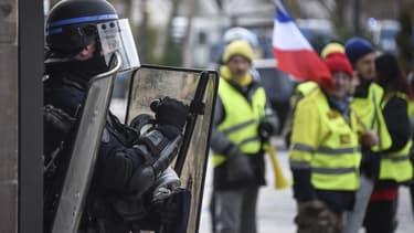 Un CRS fait face à des gilets jaunes, lors de leur 13e mobilisation à Paris le 9 février