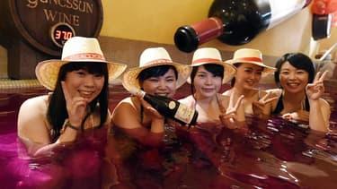 Des Japonaises posant dans un spa rempli de Beaujolais nouveau
