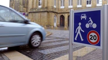 """Le panneau B52 signalant des """"zones de rencontre"""" entre piétons, cyclistes et voitures où les véhicules ne doivent pas dépasser les 20 km/h."""