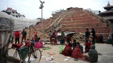 Des Népalais devant des immeubles effondrés, le 26 avril, à Katmandou.