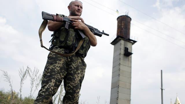 Un soldat ukrainien surveille un check-point près de la ville de Donetsk, dans l'Est de l'Ukraine, le 11 août.