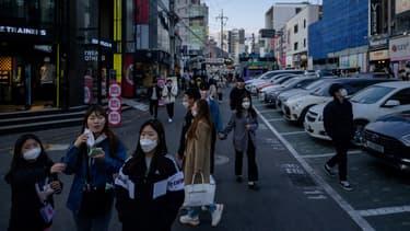 Des passants dans les rues de Séoul, le 12 avril.