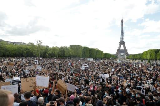 Des manifestants lors d'un rassemblement sur le Champ-de-Mars, le 6 juin 2020 à Paris, pour dénoncer le racisme et les violences policières