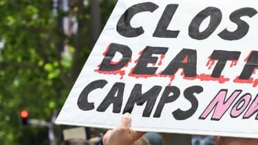 """Une manifestante pro-réfugiés à Sydney en 2015, portant une pancarte """"fermez les camps de la mort!""""."""