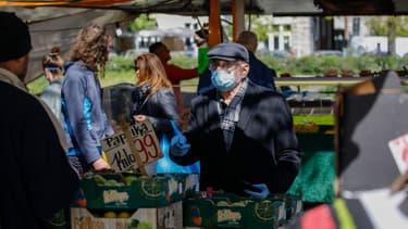 Une homme se protège avec un masque sur un marché de Berlin, le 17 avril 2020