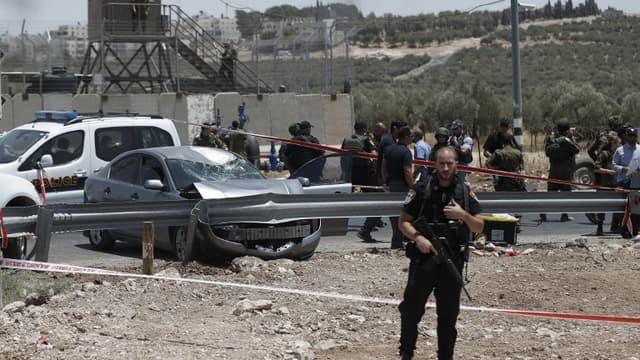 Un soldat israélien sur les lieux de l'attaque à la voiture pigée, près de la colonie de Teoka, dans le sud de Jérusalem le 10 juillet 2017.