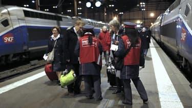 Des agents SNCF attendent à l'arrivée d'un train pour donner aux passagers des formulaires de remboursement.