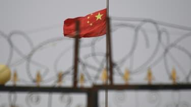 Le drapeau chinois flotte derrière des barbelés dans un complexe immobilier du Xinjiang, en Chine, en juin 2019