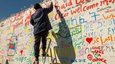 Un migrant inscrit un message sur un mur du terminal de ferry de Calais (photo d'illustration) -