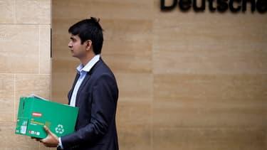 Un homme sort du bâtiment de Deutsche Bank à Londres, un carton à la main.