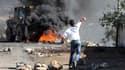 Un jeune Palestinien jette une pierre sur un bulldozer israélien pour protester contre la construction de nouvelles colonies.