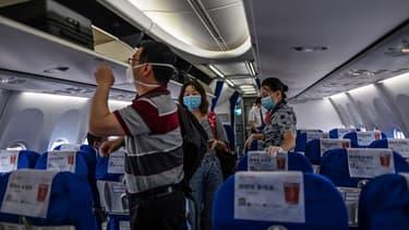Des passagers masqués à bord d'un avion faisant la liaison entre Wuhan et Shangai le 29 mai 2020.