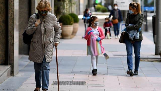Des passants portant un masque.