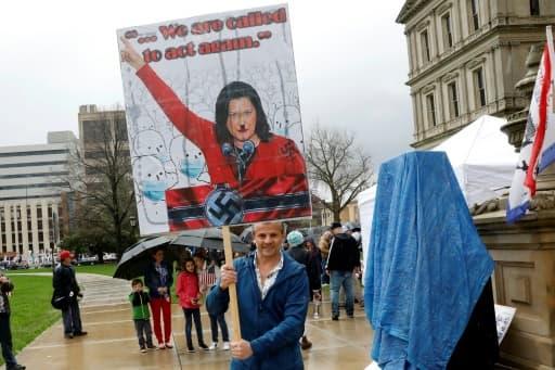 Un manifestant brandit une pancarte montrant la gouverneure du Michigan, Gretchen Whitmer, sous les traits de Adolf Hitler, lors d'une manifestation contre le confinement, le 30 avril 2020 à Lansing  pril 30, 2020