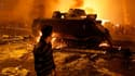 Véhicule blindé en feu dans le centre du Caire. Le président égyptien, Hosni Moubarak, a souligné vendredi soir que la frontière entre la démocratie et le chaos était mince et a déclaré que les difficultés ne devaient pas se régler par la violence. /Photo