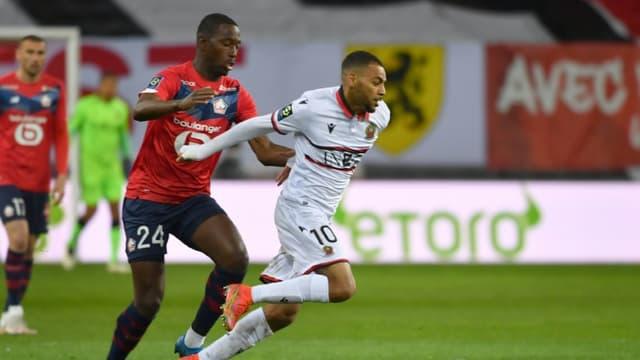 Le milieu de Lille Boubakary Soumaré (g) à la lutte avec l'attaquant de Nice Alexis Claude-Maurice, le 1er mai 2021 à Villeneuve-d'Ascq