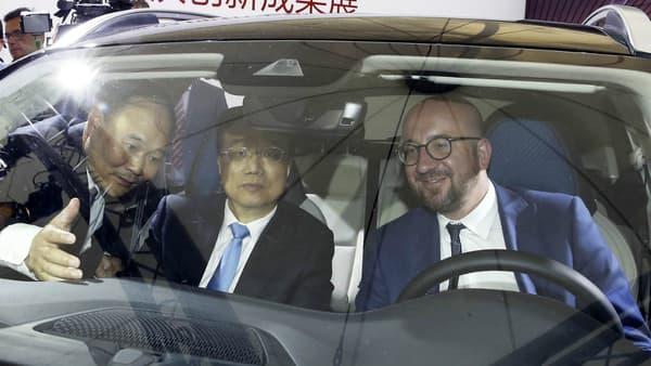 A gauche, Li Shufu présente un modèle un de ses modèlesaux premiers ministres chinois et belge Li Keqiang et Charles Michel.