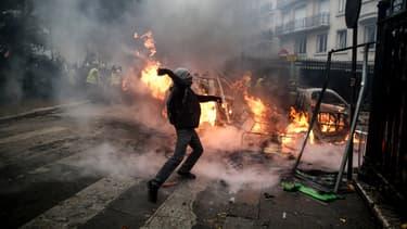 Un manifestant lance un projectile le 1er décembre 2018 à Paris, en marge du rassemblement de gilets jaunes.