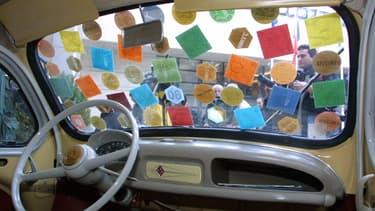 Image d'illustration - Une voiture qui porte sur son pare-brise toutes les vignettes automobiles éditées entre 1957 et 2000.