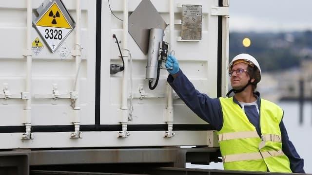 Un employé contrôle le niveau de radioactivité d'un conteneur