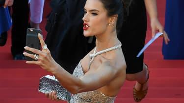 La top model Alessandra Ambrosio en train de faire un selfie sur le tapi rouge de Cannes