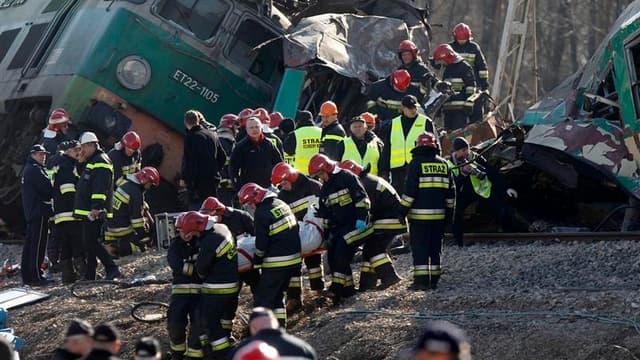 Secouristes évacuant un corps de la carcasse d'un wagon. Une collision entre deux trains de voyageurs a fait 16 morts et une soixantaine de blessés, samedi soir à Chalupki, dans le sud de la Pologne. /Photo prise le 4 mars 2012/REUTERS/Peter Andrews