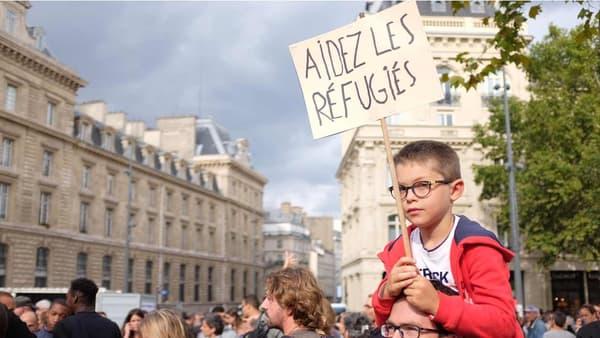 """Un petit garçon porte une pancarte: """"Aidez les réfugiés"""""""