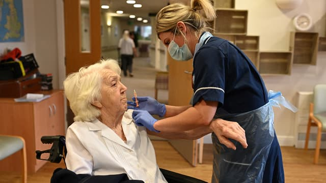 Une résidente de maison de retraite reçoit une dose de vaccin à Wigan, au Royaume-Uni, le 21 janvier 2021