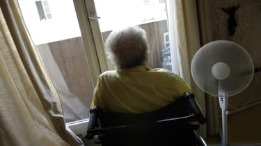 Une personne âgée se repose avec à ses côtés un ventilateur installé devant la fenêtre de son domicile à Paris, le 20 juillet 2006.