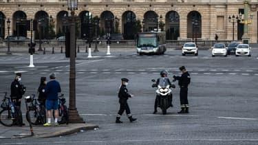 Des forces de l'ordre en train de contrôler un individu en scooter à Paris au premier jour du confinement au moins de mars 2020