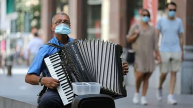Un joueur d'accordéon porte un masque dans une rue d'Antwerp, en Belgique, le 6 août 2020.