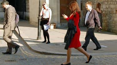 Une piétonne en train de traverser les yeux rivés sur son téléphone à Londres (Angleterre).