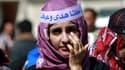 """Une jeune Yéménite manifeste son soutien à Houda, devant le tribunal de Sanaa, dimanche 24 novembre. Sur son front, le slogan """"Nous sommes tous Houda""""."""